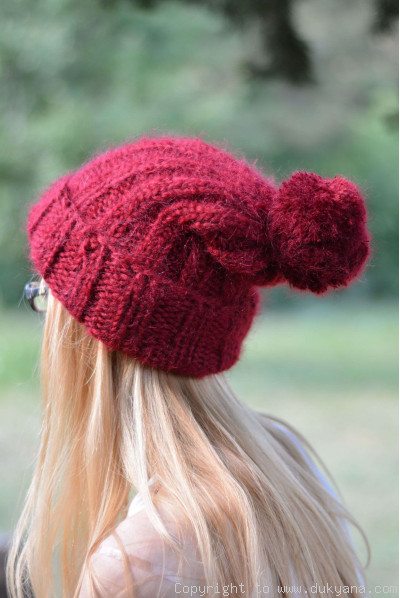 Warm winter ski hat with pompon knitted in red