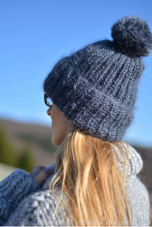 Warm winter ski hat with pompon knitted in denim blue