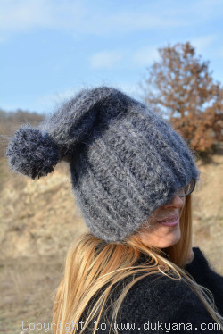 Thick winter ski hat with pompon knitted in dark gray