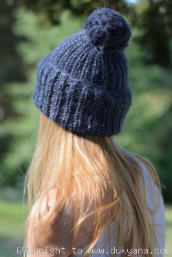 Warm winter ski hat with pompon knitted in navy blue