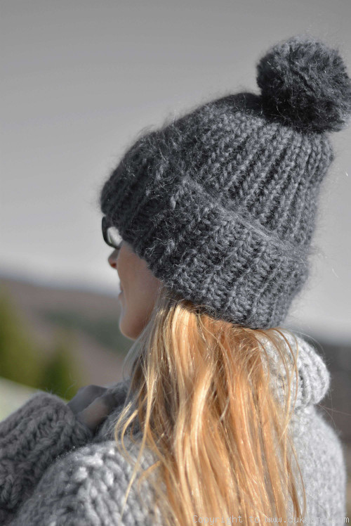 Thick winter ski hat with pompon knitted in steel gray